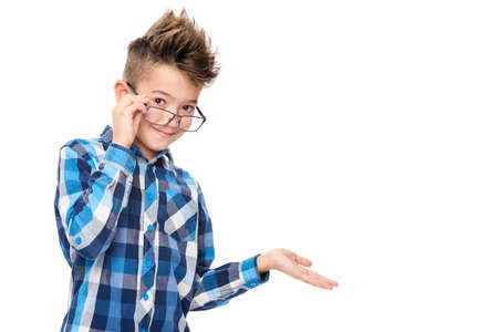 Cute smiling boy wearing reading glasses and pointing with hand to one side studio portrait on white background.