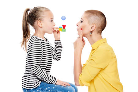 Cute young girl with speech therapist making special exercises at speech therapy office. Child speech therapy concept on white background. Speech impediment corrective exercises. Banco de Imagens