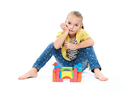Young girl at behavior therapy, building a castle with wooden toy block. Child play therapy concept on white background.