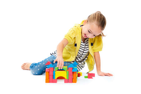 Young girl building a castle with wooden toy block. Child play therapy concept on white background.