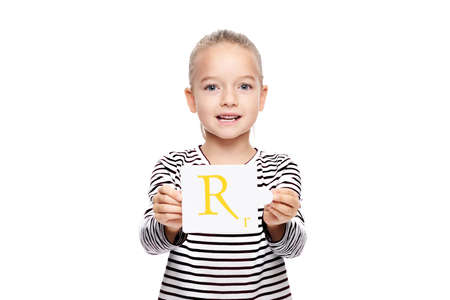 Young girl holding a card with letter R. Speech therapy concept on white background. Correct pronounciation and articulation at preschool age.