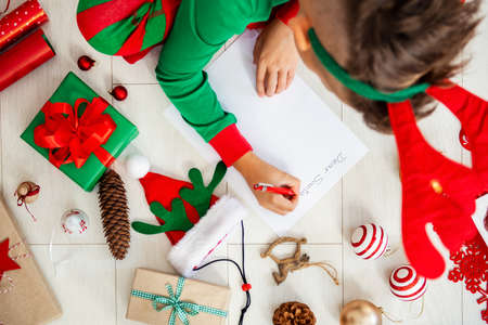 Cute boy wearing christmas pajamas writing letter to Santa on livingroom floor. Overhead view of a young boy writing his christmas wishlist. Stock Photo