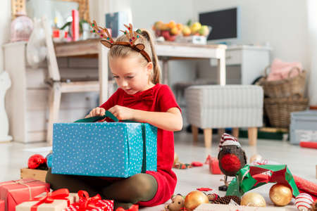 Cute super excited young girl opening large christmas present while sitting on living room floor. Candid family christmas time lifestyle background.