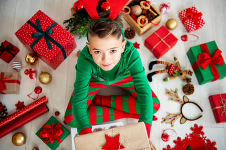Top view of a curious young boy wearing xmas pajamas sitting on the floor, holding a christmas present, looking up.