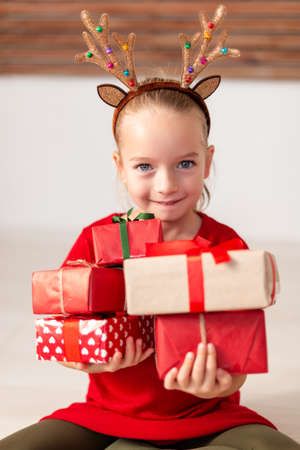 Cute young girl holding stack of christmas presents, smiling and looking at camera. Happy kid at christmas time.