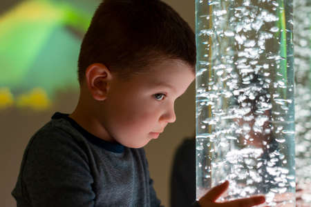 Niño en sala de estimulación sensorial de terapia, snoezelen. Niño interactuando con la lámpara de tubo de burbujas de luces de colores durante la sesión de terapia.