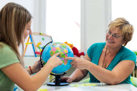 Therapist working with a teenage girl with learning difficulties. Private geography tutoring session. Teacher with teenage student in class pointing to countries on a globe.