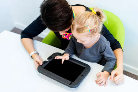 Toddler girl in child occupational therapy session doing sensory playful exercises with her therapist using digital tablet. Top view. Stock Photo