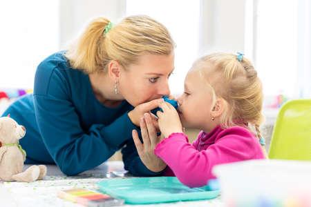 Petite fille en séance d'ergothérapie pour enfants faisant des exercices sensoriels ludiques avec son thérapeute.