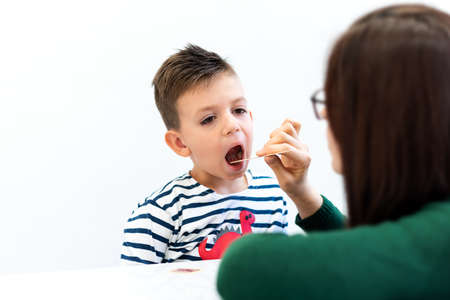 Young boy in speech therapy office. Preschooler exercising correct pronunciation with speech therapist.