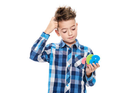 Cute boy with dyscalculia holding large colorful numbers and scratching his head. Learning disability concept on white background.