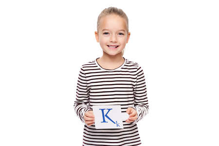 Young girl holding a card with letter K. Speech therapy concept on white background. Correct pronounciation and articulation at preschool age.