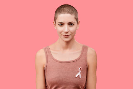 Smiling mid 30s woman, a cancer survivor, wearing pink breast cancer awareness ribbon, isolated over living coral background. Support, solidarity, screening and prevention concept. Stock Photo