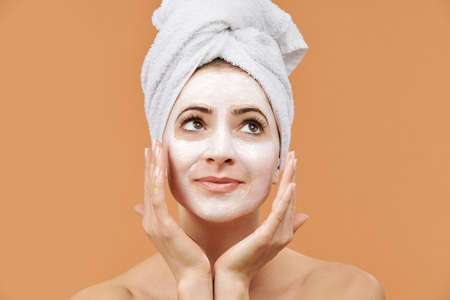 Young woman with white bath towel in her hair and mouisturizing face mask. Wellness and Spa concept on beige background. Stock fotó