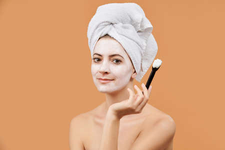 Young woman with white bath towel in her hair holding brush, applying face mask. Wellness and Spa concept on beige background. Stok Fotoğraf