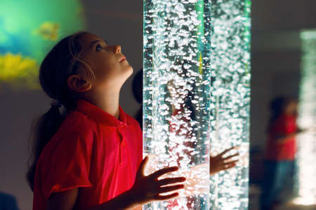 Child in therapy sensory stimulating room, snoezelen. Child interacting with colored lights bubble tube lamp during therapy session. Standard-Bild - 117932597