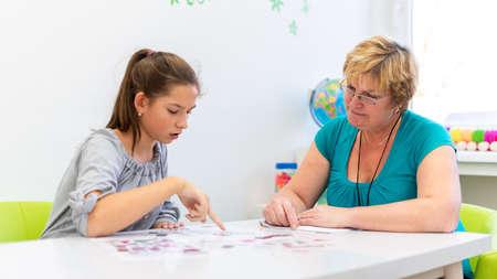 Thérapeute mature travaillant avec une adolescente ayant des difficultés d'apprentissage pour maîtriser les tests logiques.