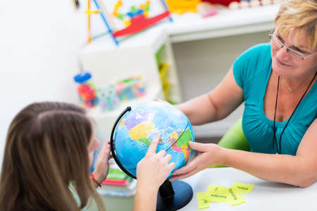 Mature female therapist working with a teenage girl with learning difficulties. Private geography tutoring session. Teacher with teenage student in class pointing to countries on a globe. 版權商用圖片