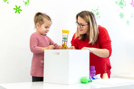 Toddler girl in child occupational therapy session doing sensory playful exercises with her therapist. Imagens