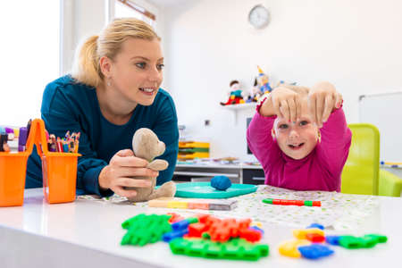 Toddler girl in child occupational therapy session doing sensory playful exercises with her therapist. 免版税图像 - 117932507