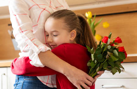 Happy Mother's Day or Birthday Background. Adorable young girl hugging her mom after surprising her with bouquet of red roses. Family celebration concept. Foto de archivo