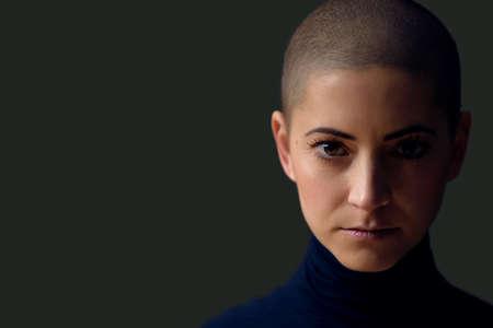 Porträt einer schönen jungen Frau mit kurzer Frisur. Herrliches weibliches Krebspatientenporträt auf dunklem Hintergrund mit Kopienraum. Standard-Bild