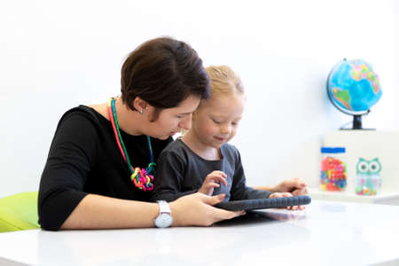 Toddler girl in child occupational therapy session doing playful exercises on a digital tablet with her therapist. Stock Photo