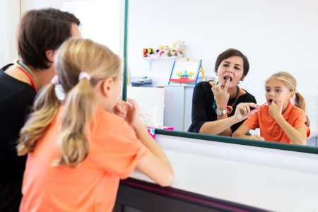 Young girl in speech therapy office. Mirror reflection of young girl exercising correct pronunciation with speech therapist.