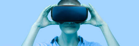 Young woman wearing virtual reality goggles. Woman wearing VR glasses over blue background. VR experience web banner.
