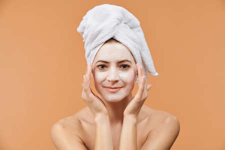 Young woman with white bath towel in her hair and mouisturizing face mask. Wellness and Spa concept on beige background. Imagens