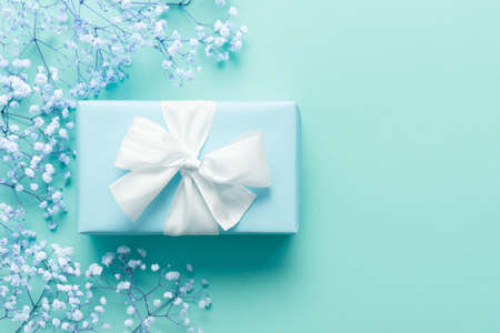 Fathers day background, blue background with white flowers and a present