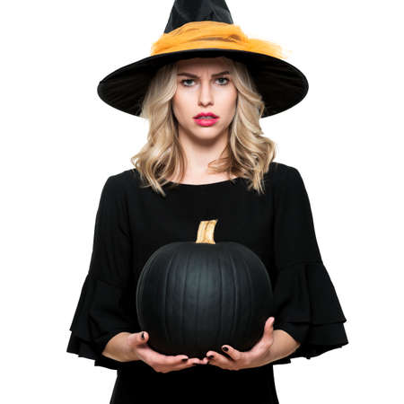 Attractive young woman in Halloween Witch costume holding large black pumpkin, looking confused. Halloween concept over white background.