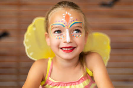 Waist up portrait of cute preschooler with DIY face paint wearing a butterfly halloween or carnival costume.
