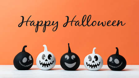Cute Little Black and White Halloween Pumpkins with smile standing side by side on white wooden table over orange background. Halloween concept. Imagens