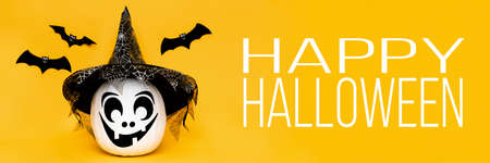 Cute smiling face Halloween Jack o Lantern and flying paper bats over yellow background. Halloween web banner. Stock Photo
