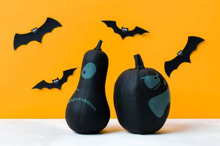 Scary black Jack o Lanterns and flying paper bats over yellow background. Halloween background. Stock Photo