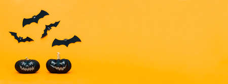 Spooky Halloween Jack o Lanterns and flying paper bats over yellow background. Halloween web banner. Imagens