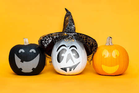 Three cute Halloween Pumpkins side by side over yellow background. Halloween background.