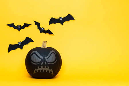 One scary black Jack o Lantern and flying paper bats over yellow background. Halloween background with copy space.