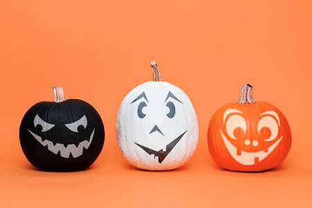 Three cute Halloween Pumpkins side by side over orange background. Halloween background.