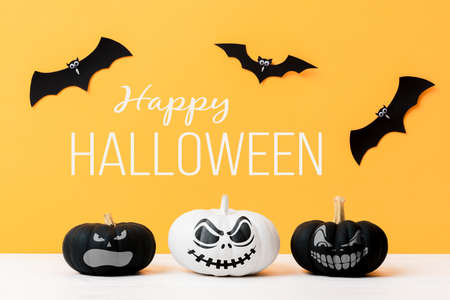 Three scary Black and White Jack o Lanterns and flying paper bats over yellow background. Halloween background.