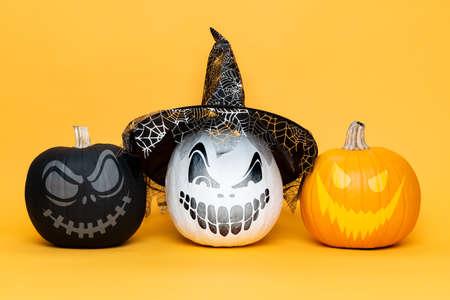 Three scary Halloween Jack o Lanterns side by side over yellow background. Halloween background.