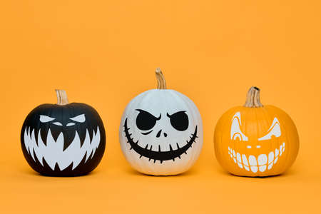 Three Spooky Halloween pumpkins with scary face expressions over orange background. Halloween concept. Imagens