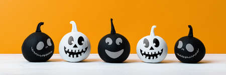Cute Little Black and White Halloween Pumpkins with smile standing side by side on white wooden table over orange background. Halloween banner.