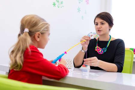 Mädchen im Grundschulalter in der Ergotherapie-Sitzung für Kinder, die mit ihrem Therapeuten spielerische Übungen machen. Standard-Bild