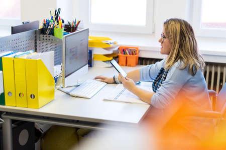 Terapeuta infantil en una oficina durante una llamada telefónica, utilizando el calendario en línea para programar citas de pacientes. Concepto de gestión de organización de planificador de calendario.