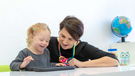 Toddler girl in child occupational therapy session doing playful exercises on a digital tablet with her therapist. Foto de archivo - 131324619