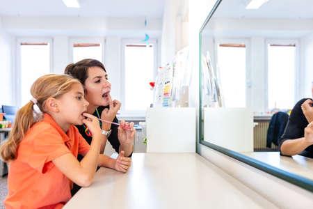 Chica joven en la oficina de terapia del habla. Reflejo de espejo de niña ejercitando la pronunciación correcta con logopeda. Foto de archivo