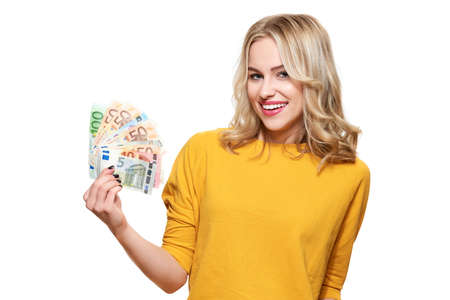 Young pretty woman in yellow sweater holding bunch of Euro banknotes, looking at camera and smiling, isolated on white background.  Stok Fotoğraf