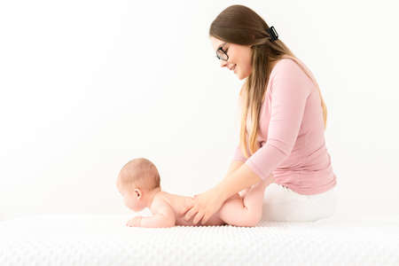 Baby massage background. Young therapist giving a baby boy a back massage.